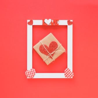 Present near frame with love title and heart symbols
