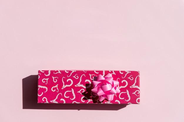 Настоящая или подарочная коробка, бумажное сердце и вид сверху ленты с розовым бантом.