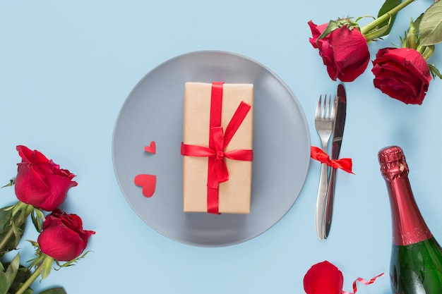 Present on plate near cutlery, roses and bottle of champagne