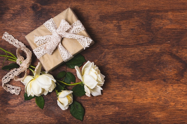 Present tied with doily and rose bouquet