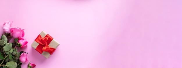 Подарок перевязанный красной лентой и букетом розовых роз на розовом фоне