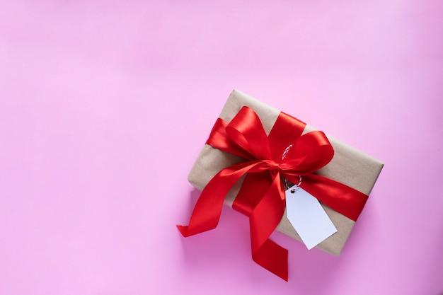 Подарок перевязан красной лентой. день святого валентина, рождество, день матери, день рождения, свадебный подарок