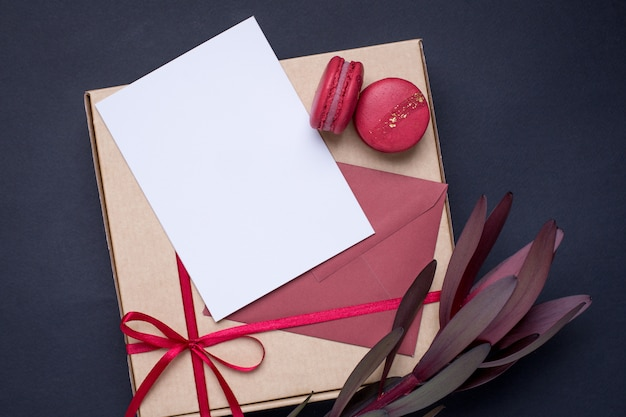 Present white card and gift in box with satin ribbon on dark