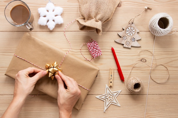 Present with christmas decorations on wooden background