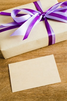 Present with empty tag on wooden background.