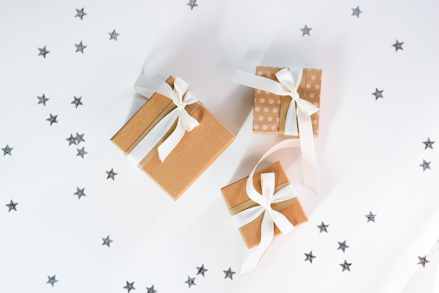 Present with white bow on white stars sparkling background. festive backdrop for holidays: birthday, valentines day, christmas, new year. flat lay