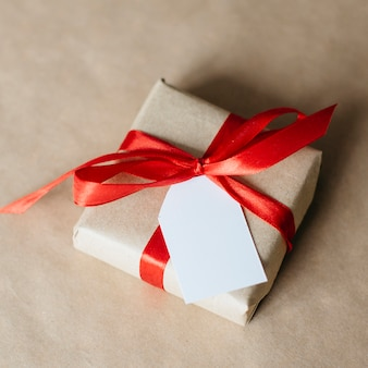 Present wrapped with red ribbon and postcard