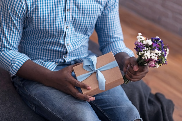 Present for you. close up of delighted man holding flowers and gift and preparing surprise for his girlfriend.
