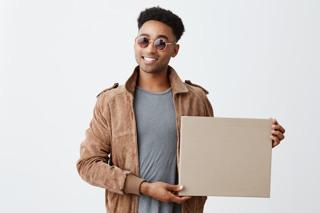 Present for you. isolated on white portrait of young fashionable dark-skinned man with afro hairstyle in grey t-shirt, brown jacket and sun-glasses holding box in hand, smiling in camera.
