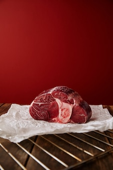 Presentation of angus leg steak on wooden table red wall