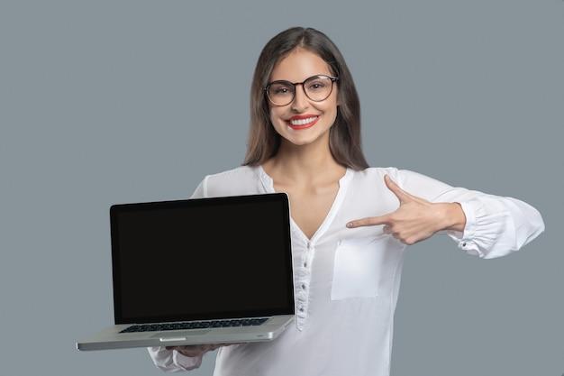 표시. 그녀의 앞에 그것을 들고 열린 노트북에서 손가락으로 가리키는 흰 블라우스에 안경에 설득력있는 즐거운 여자