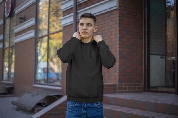 거리에 있는 젊은 남자에게 빈 검은색 후드티를 보여주고 있습니다. 온라인 상점에서 광고하기 위한 평상복 모형. 디자인과 패턴을 위한 템플릿 긴팔 후드
