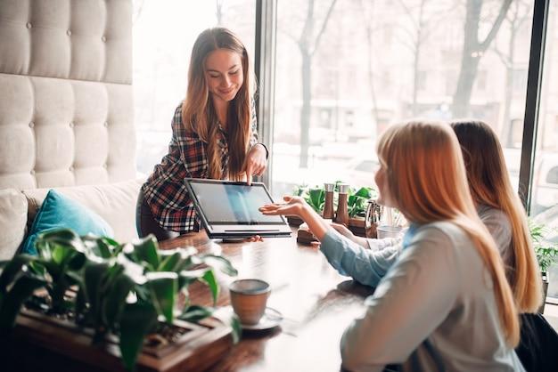 Презентация товаров на ноутбуке, встреча с покупателями за обедом в кафе. современные рекламные и маркетинговые технологии