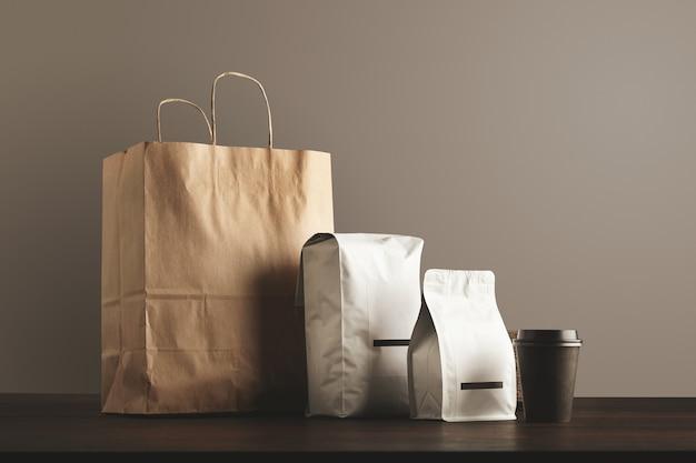 Презентация комплекта розничной торговли. крафт-бумажный пакет, большой мешочек, маленький контейнер и стакан с крышкой.