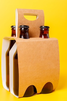 Presentation of pack of four beers with yellow background