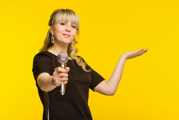 Presentation, public speech, conference, broadcasting, advertising. cheerful young businesswoman, reporter, tv presenter holding microphone isolated bright yellow background. focus on mic