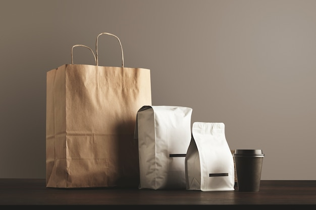 Presentation of retailer package set. craft paper bag, big pouch, small container and take away glass with cap.