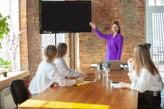 표시. 팀과 함께 현대 사무실에서 젊은 백인 비즈니스 여자. 회의, 과제 제공. 프론트 오피스에서 일하는 여성. 금융, 비즈니스, 여성의 힘, 포용, 다양성, 페미니즘의 개념.