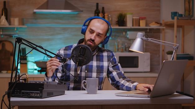 Presentatore che parla di passioni e intrattenimento in podcast indossando le cuffie. spettacolo online creativo produzione in onda trasmissione internet host in streaming di contenuti live, registrazione di social media digitali