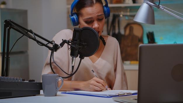 발표자는 클립보드에 글을 쓰고 전문 마이크를 사용하여 팟캐스트를 녹음하는 동안 헤드폰을 착용합니다. 크리에이티브 온라인 쇼 온에어 프로덕션 인터넷 방송 호스트 스트리밍 라이브 콘텐츠, 녹화