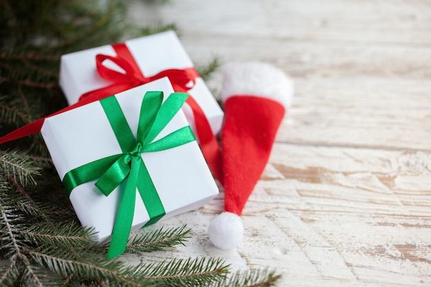 クリスマスホワイトボックスまたは白い木製のテーブルの上のサンタの帽子とpresentes。