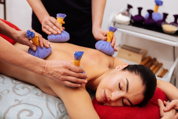Presenting naked back. calm young woman with closed eyes getting meditative session in professional beauty salon