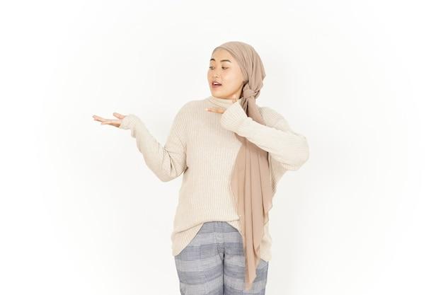 Представляя продукт на открытой ладони красивой азиатской женщины в хиджабе, изолированной на белом фоне