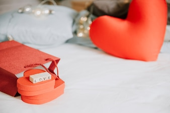 Presents and heart cushions on bed