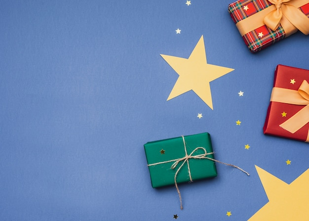 Presents for christmas on blue background with golden stars