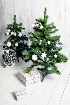 Presents under decorated christmas trees in white interior.