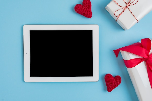 Presents and knitted hearts near modern tablet