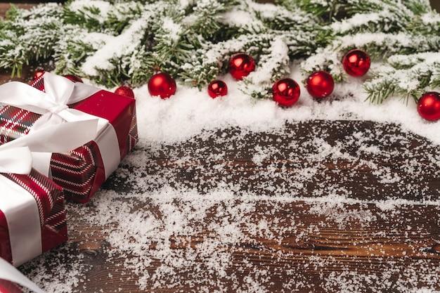 전나무 나무 가지와 눈으로 가루 빨간 지팡이와 나무 배경에 선물