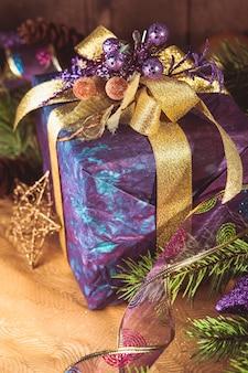 メリークリスマスと新年あけましておめでとうございますの木製の背景にプレゼント