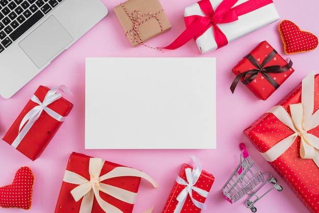 Presents and shopping trolley near paper sheet and laptop