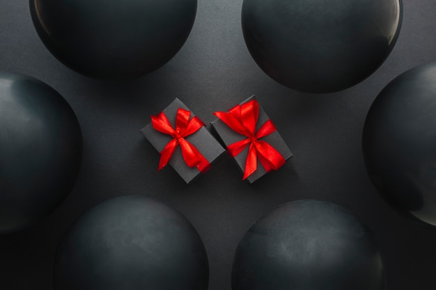 Presents surrounded by black balloons