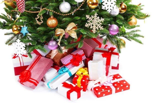白で隔離のクリスマスツリーの下にプレゼント