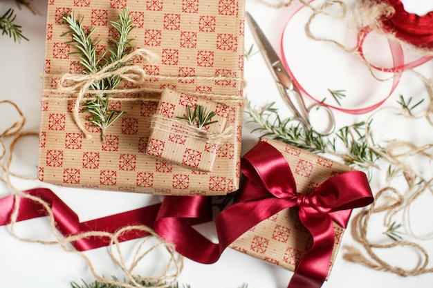 Подарки, завернутые в бумагу и украшенные лентами и розмарином, вид сверху