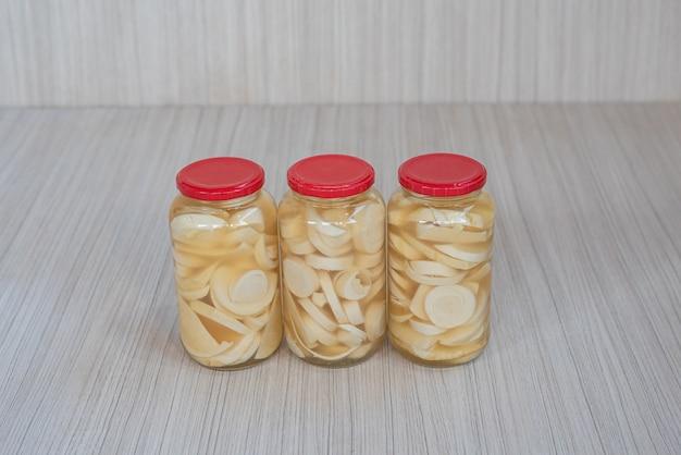 Варенье из гуарироба внутри горшка на белой деревянной поверхности