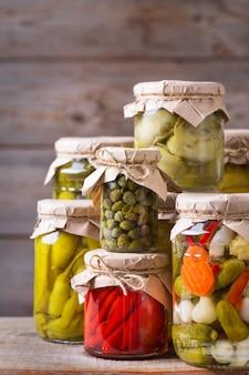 Консервированные и ферментированные продукты. ассортимент самодельных банок с различными маринованными и маринованными овощами на деревянном столе. домоводство, домоводство, сохранение урожая