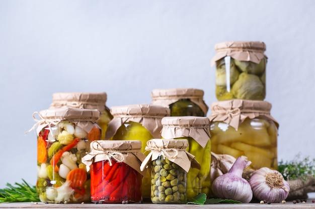 보존 및 발효 식품. 다양한 절인 야채와 절인 야채를 나무 테이블에 넣은 수제 항아리 구색. 가사, 가정 경제, 수확 보존