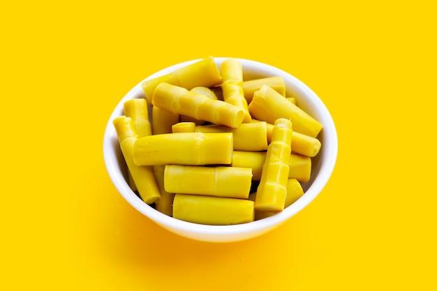 黄色の背景に白いボウルに保存されたタケノコ。