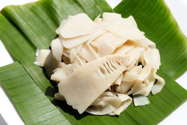 白いプレートのバナナの葉に保存されたタケノコ