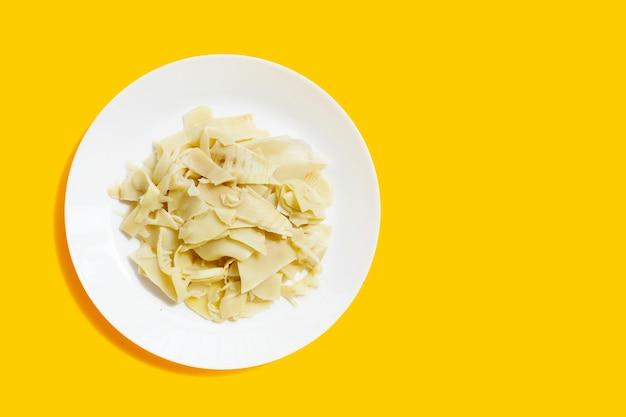 Сохраненные ломтики побегов бамбука в белой тарелке на желтом фоне.