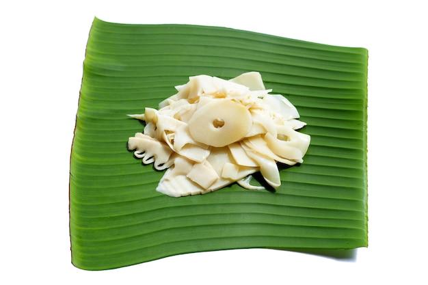 白い背景の上のバナナの葉に保存されたタケノコのスライス。