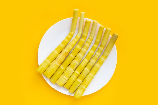 Preserved bamboo shoot in white plate on yellow background.