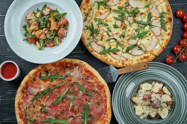 さまざまな料理の保存されたダイニングテーブル:黒い表面にピザ、シーザーサラダ、シーフードサラダ。トップビュー、食品フラットレイアウト