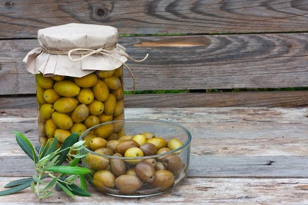 木製の背景にガラスの瓶とボウルに保存された発酵オリーブ。秋の野菜の缶詰。