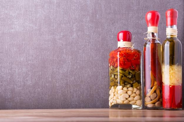 木製の棚の上のガラス瓶に保存された食品。各種マリネ