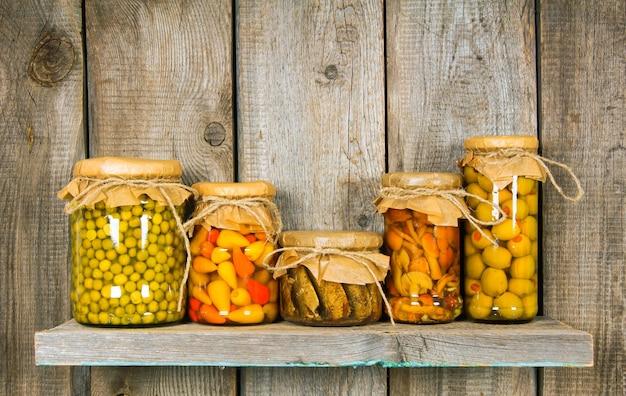 木製の棚にあるガラスの瓶に保存された食品。さまざまなマリネ料理