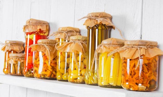木製の棚の上のガラスの瓶に保存された食品。さまざまなマリネ料理
